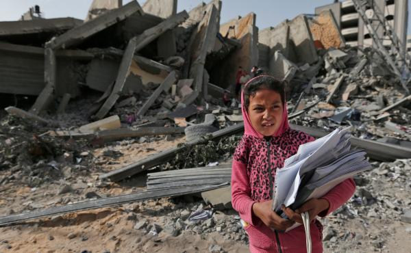 Palestinian leaders in Gaza report that they've agreed to a cease-fire with Israel to end a deadly two-day escalation of violence. Here, a Palestinian girl stands in front of a building on Monday that was destroyed during Israeli airstrikes on Gaza City o