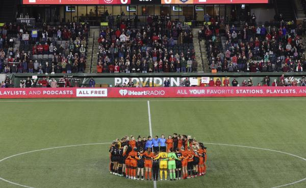 Portland Thorns and Houston Dash players, along with referees, gather at midfield, in demonstration of solidarity with two former NWSL players who came forward with allegations of sexual harassment and misconduct against a prominent coach, during an NWSL