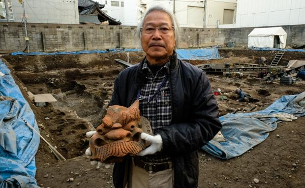 Archaeologist Koji Iesaki holds a carved roof ornament excavated at the former site of the Jyokyo-ji temple in Kyoto, Japan. Iesaki and other archaeologists have their hands full as a pre-Olympic building boom has helped reveal centuries-old artifacts fro