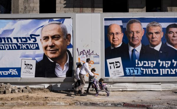 People walk by election campaign billboards showing Israeli Prime Minister and head of the Likud party Benjamin Netanyahu (left) alongside the Blue and White party leaders, including Benny Gantz. Ahead of Tuesday's election, Netanyahu has pledged to annex