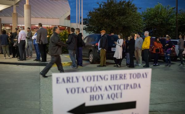 People wait in line to vote at a polling place on the first day of early voting on Oct. 22 in Houston. Texas Attorney General Ken Paxton has been aggressively prosecuting people for voting violations, which critics argue is designed to intimidate non-whit