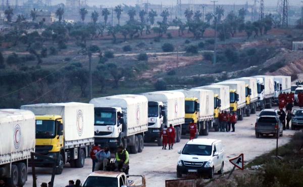 A convoy of vehicles carrying humanitarian aid sent by the United Nations moves toward the villages of Fua and Kafraya in Syria's Idlib province.
