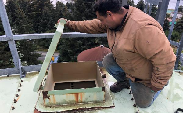 "Resident Anthony Brewster checks to see how much water is in Nanwalek's storage tank. The village has been on a ""boil water"" notice for weeks."