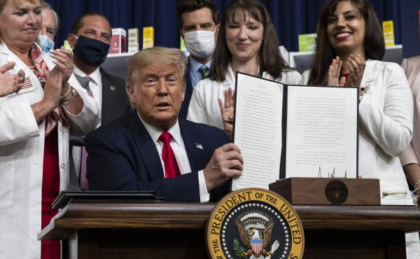 President Trump holds up a signed executive order on lowering drug prices on July 24.