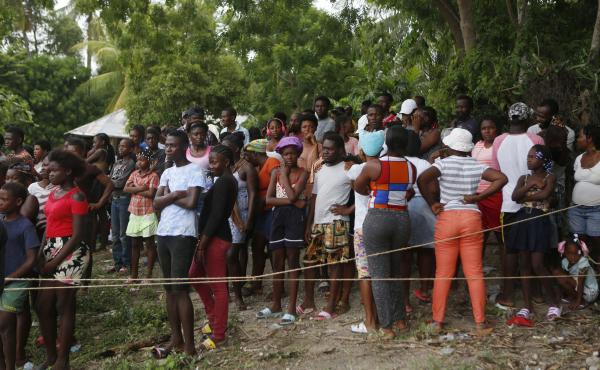 Families wait to receive humanitarian aid from a U.S. Army helicopter unit in the town of Anse-A-Veau, Haiti, on Wednesday.