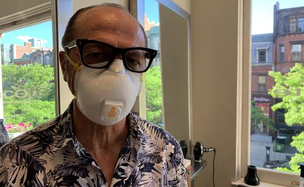 """Vincent Cox in the salon where he works that's reopened in Boston. Eighty percent of COVID-19 deaths have been in people his age or older. """"It's been one of the hardest things I've ever done in my life,"""" he says."""