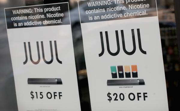 Signs in a Chicago shop window advertise e-cigarettes and pods from Juul in September. Altria, the parent company of Philip Morris, announced Thursday it would buy a 35 percent stake in the company.