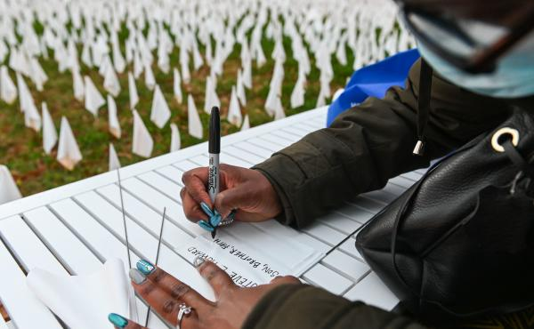 """Patrice Howard writes on white flags before planting them to remember her recently deceased father and close friends in November at """"IN AMERICA How Could This Happen...,"""" a public art installation in Washington, D.C. Led by artist Suzanne Firstenberg, vol"""