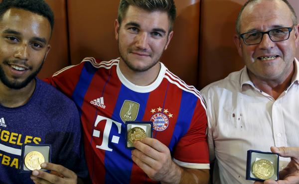 Three men who helped to disarm an attacker on a train from Amsterdam to France, from left to right, Anthony Sadler, Alek Skarlatos and Chris Norman, a British man living in France, pose with medals they received for their bravery at a restaurant in Arras,