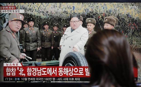 A woman watches a news program showing North Korean leader Kim Jong Un.