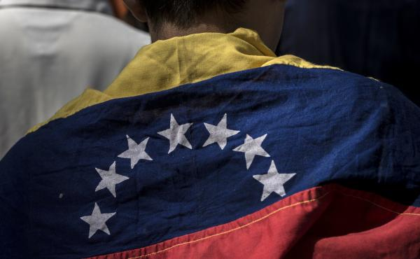 An attendee wears a Venezuelan flag during a rally in Caracas Friday with Juan Guaido, president of the National Assembly, who swore himself in as the leader of Venezuela.