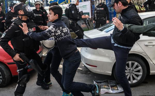 A plainclothes police officer kicks a demonstrator as Turkish anti-riot police disperse supporters in front of the headquarters of the Turkish daily Zaman newspaper in Istanbul on March 5. Turkish authorities seized the headquarters in a midnight raid.