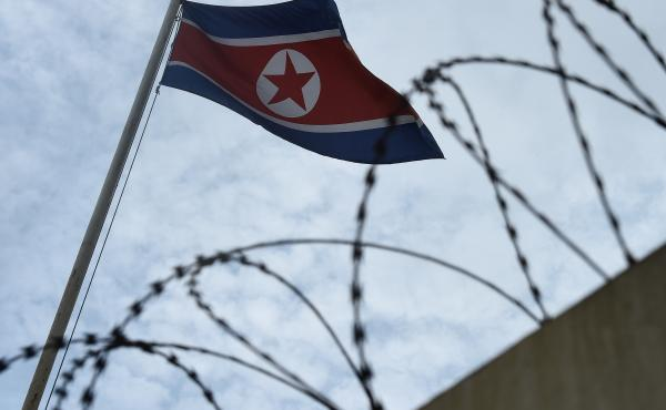 The North Korean flag flaps behind barbed wire at the North Korean Embassy on Sunday in Kuala Lumpur, Malaysia.