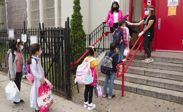 Students line up outside P.S. 179 in the Kensington section of Brooklyn, in New York City, to have their temperatures checked on the first day of in-person instruction, on Sept. 29. This Thursday, New York City public schools will be halting in-person ins