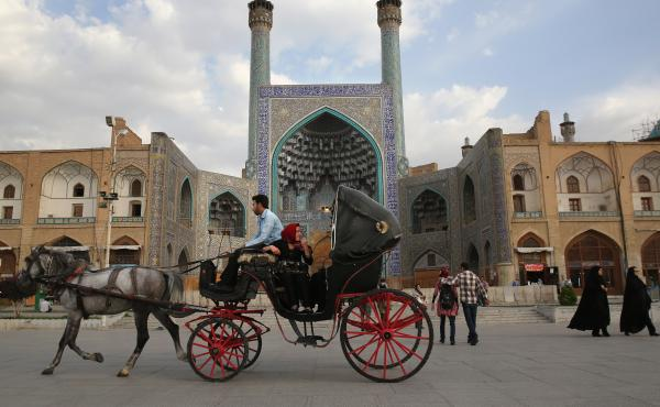 People ride a horse and carriage at sunset in Isfahan's UNESCO-listed central square on June 2, 2014 in Isfahan, Iran. Isfahan, with its immense mosques, picturesque bridges and ancient bazaar, is a virtual living museum of Iranian traditional culture, an