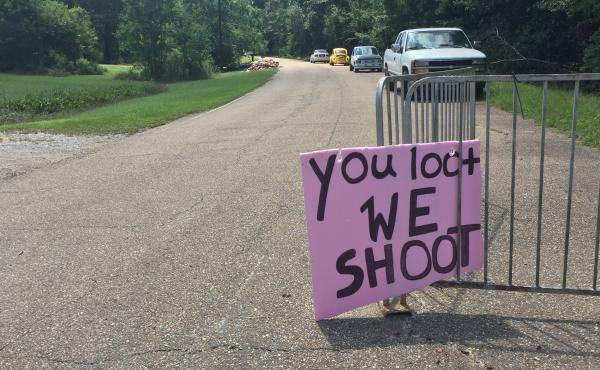 A handmade sign offers a stern warning at the entrance to an abandoned neighborhood where people have lost so much.