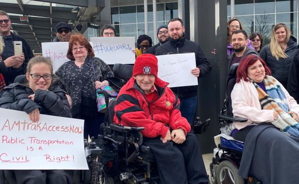 Members of the Illinois Network of Centers for Independent Living (INCIL) demonstrate in front of the Bloomington-Normal Amtrak station in Illinois to demand the suspension of an Amtrak policy that led to exorbitant fees for removing train seats to accomm