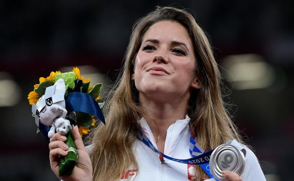 Poland's Maria Magdalena Andrejczyk celebrates her silver medal in the javelin throw at the Olympic Stadium in Tokyo on Aug. 7. She auctioned the medal to help fund heart surgery for an 8-month-old; the buyer decided to let her keep it.