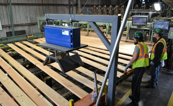 Workers watch as wooden boards move across a wood planer inside Seneca Sawmill Company in Eugene, Ore. It sits in the state's 4th congressional district — which Donald Trump almost won.