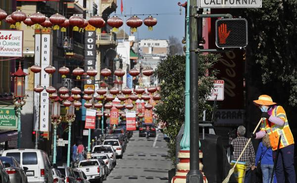 In this Jan. 31, 2020, file photo, a masked worker cleans a street in the Chinatown district in San Francisco. Police and volunteers have increased their street presence after a series of violent attacks against older Asian residents in Bay Area cities st