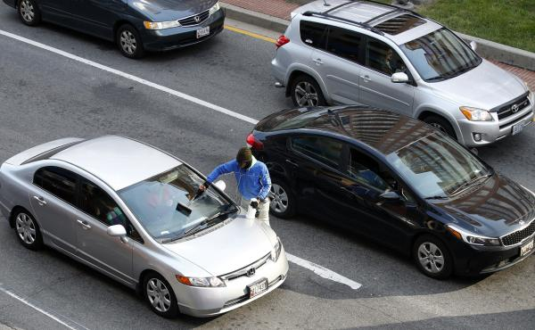 A young man washes a windshield as motorists wait at a red light in October in Baltimore.