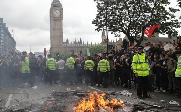 Placards are burned at the End Austerity Now rally in Parliament Square, London. Protesters have said the march was the start of a broader campaign to end government cuts to social programs.