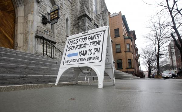 A sign sits on a sidewalk outside the Interfaith Food Pantry at Emmanuel Baptist Church in February in Albany, N.Y. Congress may be under more pressure than usual to cut safety net spending — health care, housing assistance, welfare and food aid — to