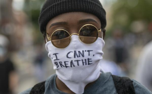"Protests over police treatment of black people have sparked concerns about the spread of COVID-19. Here, a protester marches Monday in Philadelphia with a cloth mask saying, ""I can't breathe."""