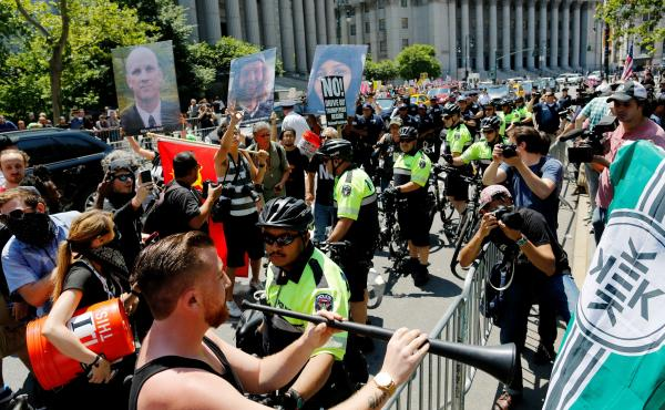 """NYPD officers try to separate counter-protesters and activists rallying for the """"March Against Sharia"""" on Saturday in New York City."""