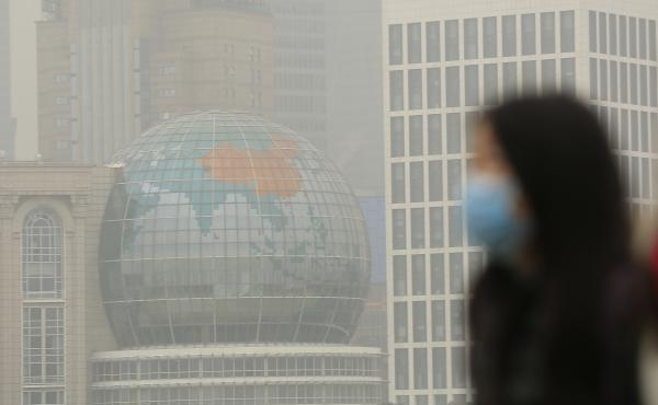 A woman wears a face mask on a hazy January day in downtown Shanghai. China has ordered a popular anti-pollution film removed from major online outlets. In Xi'an, two people who had protested against smog were reportedly detained.