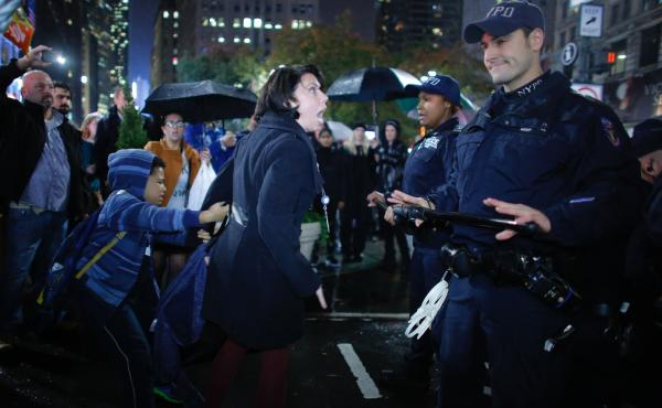 A woman argues with NYPD officers as she takes part in a protest against President-elect Donald Trump in New York City tonight.
