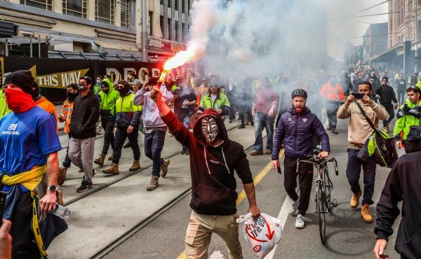 Protesters march through Melbourne, Australia, on Tuesday over recently announced COVID-19 vaccine requirements for construction workers. Construction sites have been shut down for two weeks due to protests and rising COVID-19 cases.
