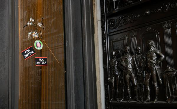 """Stickers reading """"Fck Antifa"""" are stuck on a broken window at the U.S. Capitol after the building was breached by rioters on Jan. 6."""