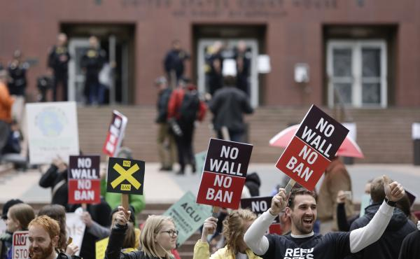 People protest outside as the 9th U.S. Circuit Court of Appeals prepares to hear arguments on President Trump's revised travel ban in Seattle on Monday.