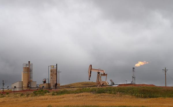 Pump jacks and a gas flare are seen near Williston, N.D., in 2016.