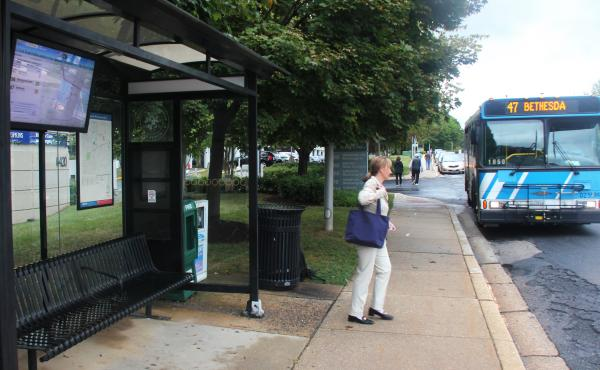 Mary Lee Kingsley is waiting for a bus in Montgomery County, Md. The bus stop has a big LED screen with a map displaying the current location of buses and when they will arrive.