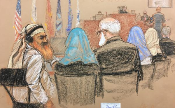 Alleged Sept. 11 mastermind Khalid Sheikh Mohammed (far left) consults with his defense attorneys in the U.S. military courtroom in Guantánamo Bay, Cuba, as a man who waterboarded him, retired Air Force psychologist James Mitchell, takes the stand.