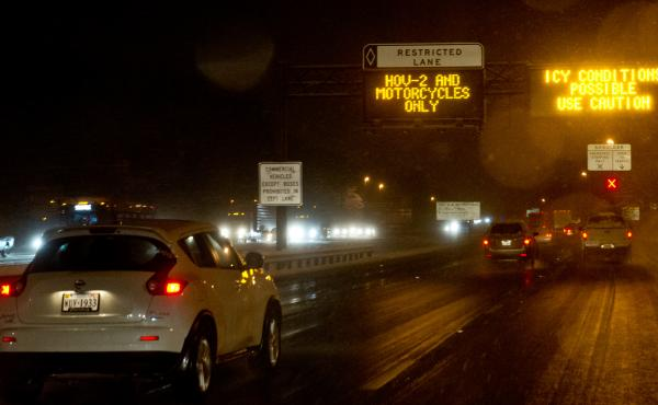 Signs warn drivers of icy road conditions on Interstate 66 in Fairfax County, Va., in March 2014. The state's Department of Transportation recently added rush hour tolls to the road, using dynamic pricing, which continuously adjusts the cost based on cong
