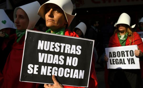 Abortion-rights supporters demonstrate earlier this month outside the National Congress in Buenos Aires, adding the legalization campaign's distinctive green handkerchiefs to outfits alluding to the dystopian novel The Handmaid's Tale. The book's author,
