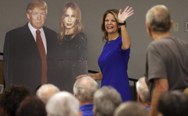 GOP Senate candidate Kelli Ward waves to volunteers and voters as she walks past a cardboard cut-out of President Donald Trump and first lady Melania Trump during the Sun Lakes Republican Club meeting in Sun Lakes, Ariz., on May 8. She's accused front-run