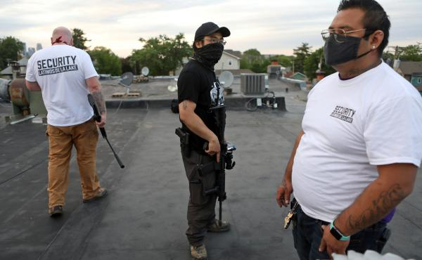 Armed volunteers take up rooftop positions in a Minneapolis neighborhood; those who are not allowed to carry guns are kept off the rooftop.