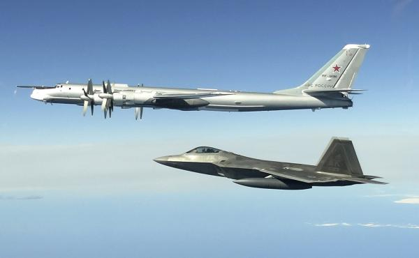 In this image taken June 16, 2020, and released by the North American Aerospace Defense Command, a Russian Tu-95 bomber (top) is intercepted by a U.S. F-22 Raptor fighter off the coast of Alaska. Russian nuclear-capable strategic bombers have flown near A