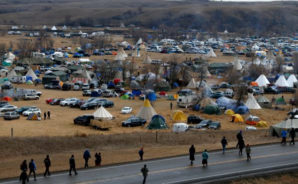 Protesters — or water protectors, as they identify themselves — walk along Highway 1806, past a sprawling encampment at Standing Rock on Thursday. Thousands of people gathered to join the Standing Rock Sioux Tribe's protest of the Dakota Access Pipeli