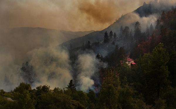 A house is covered in pink fire retardant as the Cranston Fire burns out of control near the town of Idyllwild in the San Bernardino National Forest on Wednesday.