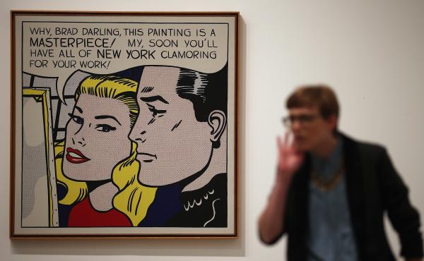 """A visitor stands in front of Masterpiece during a press preview of """"Lichtenstein, a Retrospective"""" at the Tate Modern in London in 2013. The iconic painting was owned by Agnes Gund, who recently sold it to fund a new criminal justice reform fund."""