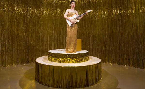 Ragnar Kjartansson's Woman in E takes place in a circular room built from a gold tinsel curtain. Unlike many of his works, Woman in E features real people, rather than films.