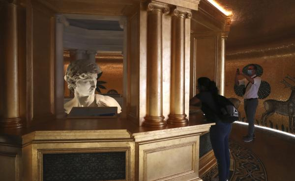 In this Friday, Oct. 1, 2021 file photo, visitors take photos of the 3D re-production of Michelangelo's David at the Italy's pavilion at the Dubai Expo 2020 in Dubai, United Arab Emirates. One of the most talked about attractions at the world's fair under