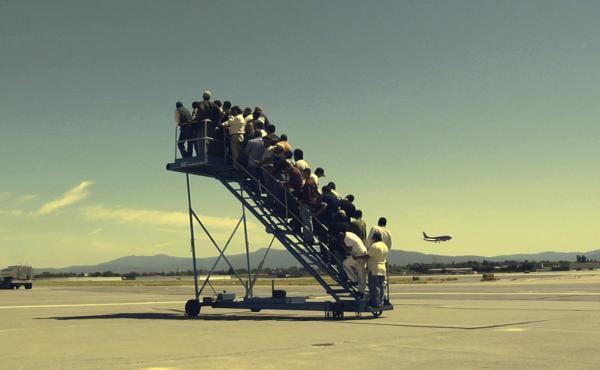 Men wait to board a non-existent plane in Adrian Paci's 2007 video, Centro di permanenza temporanea (Temporary Detention Center).