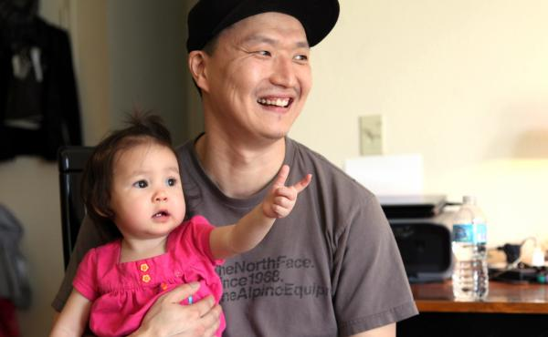 South Korean adoptee Adam Crapser poses with his 1-year-old daughter, Christal, in the family's living room in Vancouver, Wash., in 2015. Crapser, who was flown to the U.S. nearly 40 years ago and adopted by an American couple at age 3, has been ordered d
