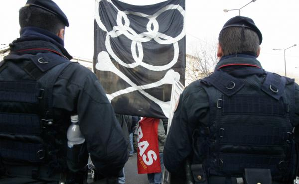 Italian military police officers stand in front of anti-Olympics demonstrators in February 2006 in Turin, Italy, on the eve of the opening ceremony of the 2006 Winter Games.